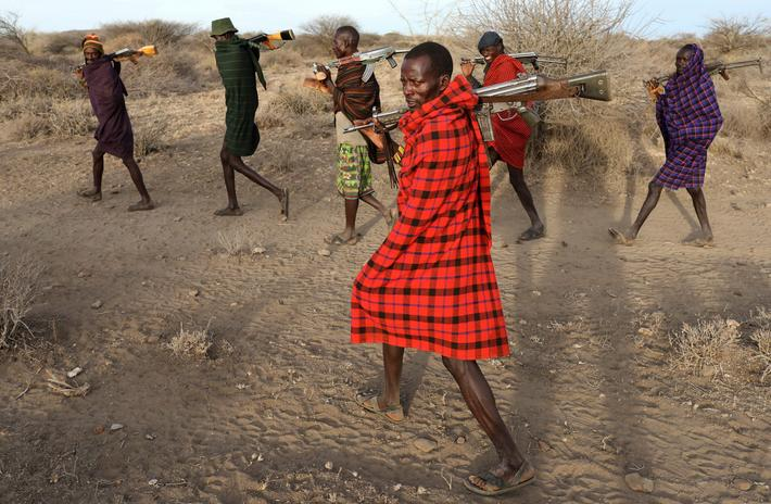 Turkana tribesmen walk with guns in order to protect their cattle from rival Pokot and Samburu tribe