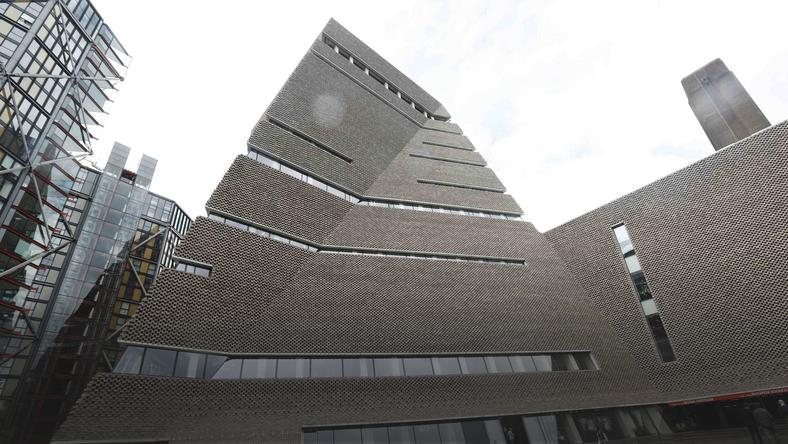 People walk past the Switch House during the unveiling of the New Tate Modern in London