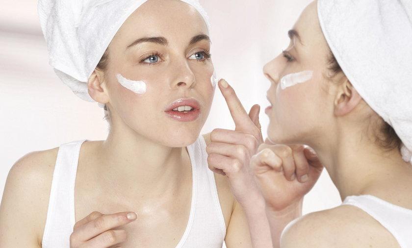 Kobieta kremująca twarz przed lustrem