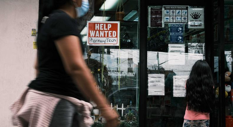 People walk by a Help Wanted sign in the Queens borough of New York City on June 04, 2021 in New York City.