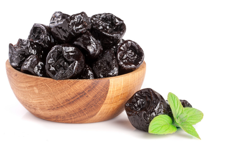 stock-photo-dried-plums-or-prunes-with-a-mint-leaf-in-wooden-bowl-isolated-on-white-background-671848381