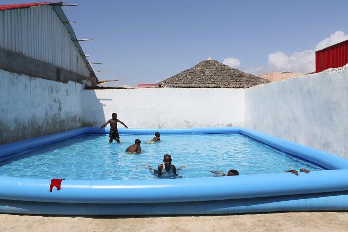 Children play in a swimming pool at a guest hotel in Mogadishu October 16, 2013. Street lamps now br