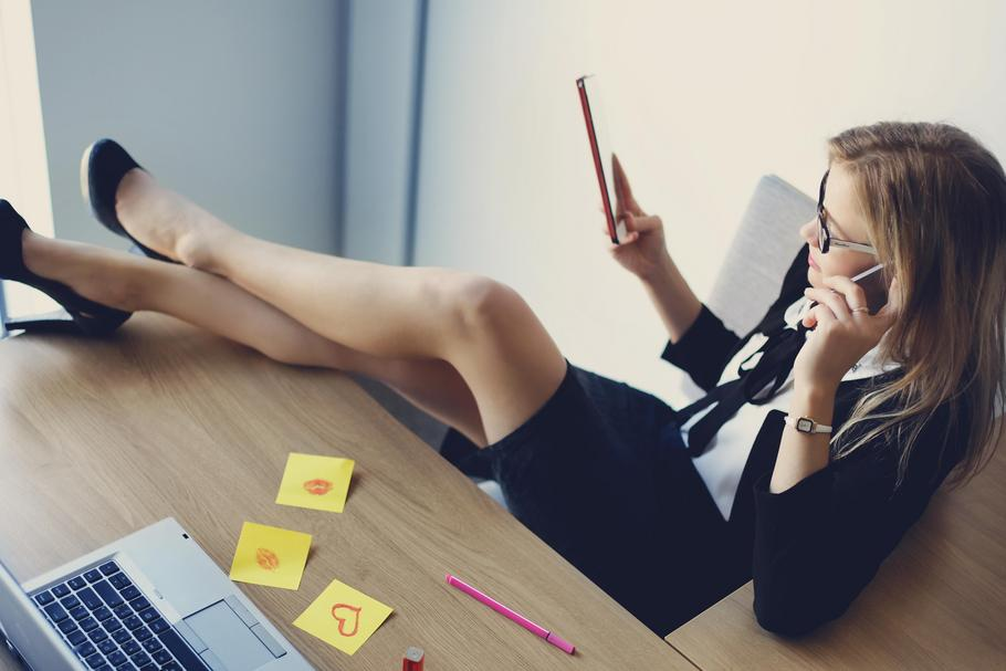 Hot business woman sitting in office with legs on table