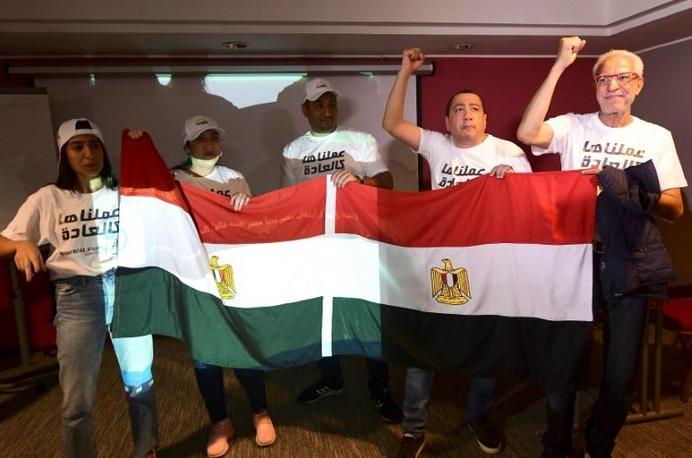 Egyptian representatives wave their national flag as they celebrate the Confederation of African Football executive committee's decision to choose Egypt to host the 2019 Africa Cup of Nations in Dakar on January 8, 2019