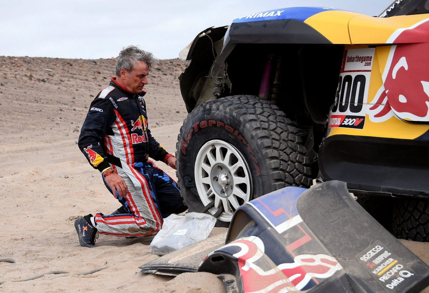 Driver Carlos Sainz, of Spain, and co-driver Lucas Cruz, of Spain, work on their Mini after it broke