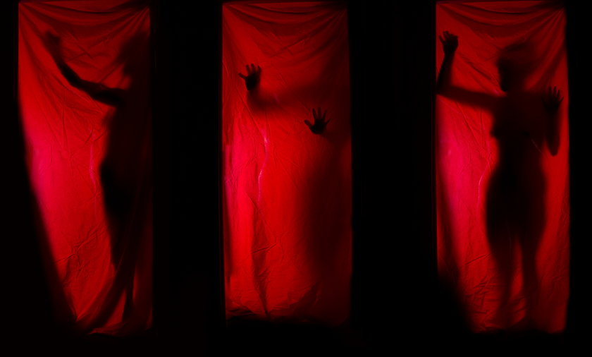 Woman behind red curtains