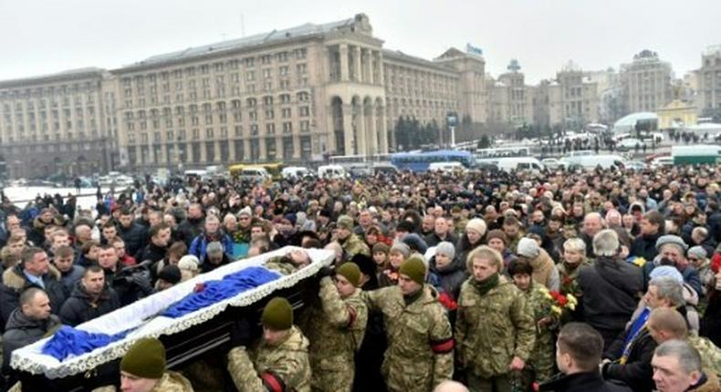 Mourners gather in Kiev's Independence (Maidan) Square on February 1, 2017, as servicemen carry the coffins of soldiers killed in eastern Ukraine