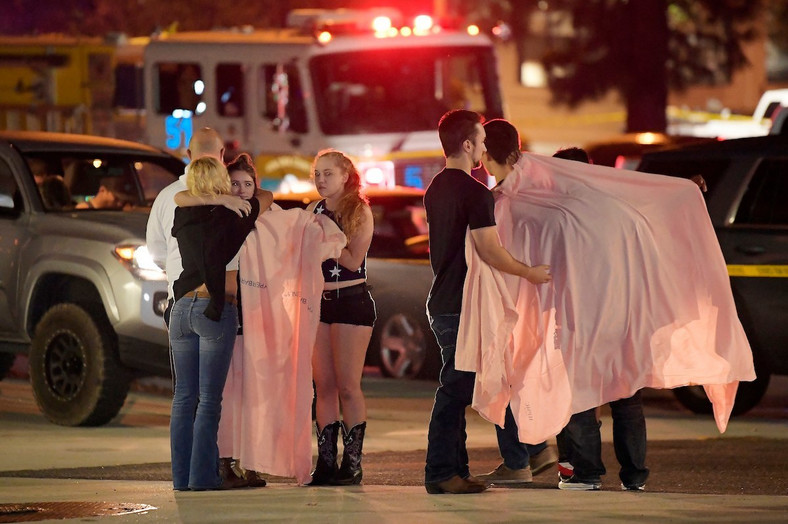 People comfort each other near the scene of the bar shooting in Thousand Oaks, California.