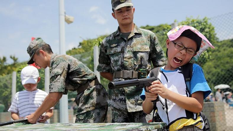 A child reacts as he pretends to use a handgun while under guidance by a Peoples' Liberation Army (PLA) soldier at the Ngong Shuen Chau Barracks in Hong Kong on July 1, 2015.