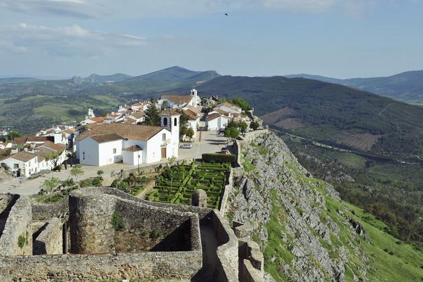 Marvão Zaledwie dwie i pół godziny jazdy od Lizbony, w wąwozie niedaleko granicy z Hiszpanią, znajduje się niewielka osada otoczona murami. To najwyżej położona wioska w Portugalii, którą zwykło określać się jako gniazdo orła ukryte w górach. Marvão, z panoramicznym widokiem na rozległe równiny regionu Alentejo, to jedno z najładniejszych miejsc w całej południowej Europie. Koniecznie trzeba zobaczyć tutejszy zachód słońca – światło odbijające się od kwarcu w granitowych głazach, które podtrzymują ogromne mury zamku, daje żywe, niemal jarzące się kolory, a także słynne fortyfikacje. – Pierwsze fortyfikacje wzniesione zostały tutaj przez Maurów w ósmym wieku. Do dziś XIII-wieczne mury zachowały się praktycznie nietknięte. Do osady prowadzi z nich wąskie, średniowieczne przejście, przy którym znajduje się ciekawie ukształtowany mauretański budynek zwany kaplicą jerozolimską. Jego wnętrze przez setki lat nie było modernizowane, nie zmieniło się tam nic. Na szczycie znajduje się piękna, niska dzwonnica z maleńką kopułą. Wyjątkowym elementem jest także piękna drewniana galeria, a na jednym z bocznych ołtarzy znajduje się niezwykły posąg Trójcy Przenajświętszej – mówi Piotr Wilk z biura podróży Rainbow. Z twierdzy zamkowej widać całą okolicę – leżące na południu Serra de São Mamede i urocze miasto Estremoz, na północy góry Serra da Estrela (góry Gwiazd) z Castelo de Vide na północnym zachodzie, a na północnym wschodzie, za horyzontem roztacza się już Hiszpania. Źródło: r.pl/portugalia >>>