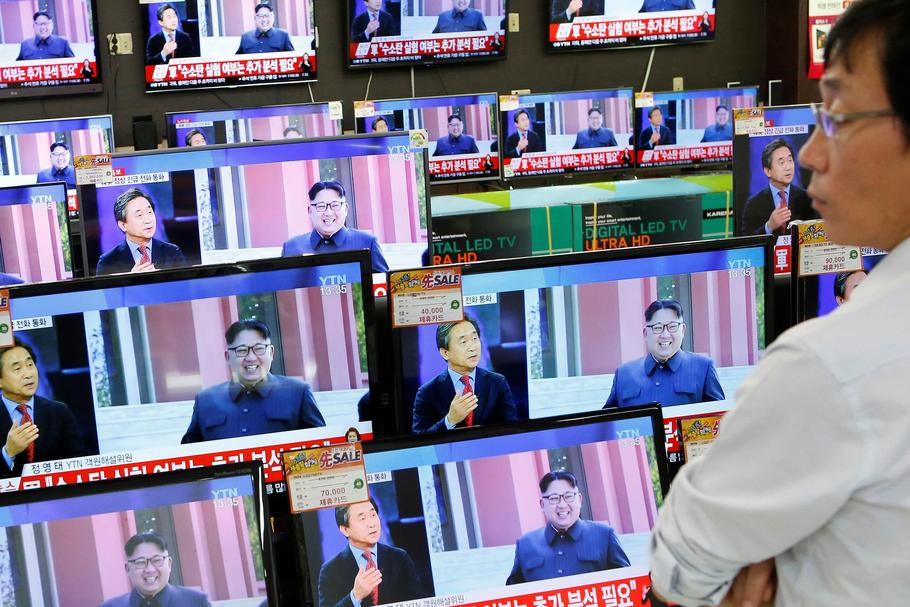 A sales assistant watches TV sets broadcasting a news report on North Korea's fifth nuclear test, in