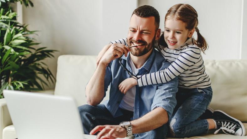 Ojciec z córką pracuje przy komputerze. Home office