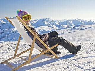 Girl sunbathing in a deckchair, snowy mountain landscape