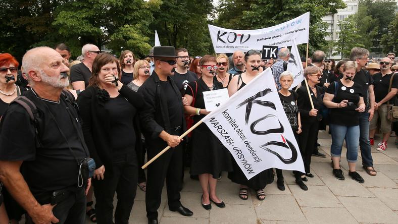 """Protestujący przed Sejmem zakleili sobie usta czarną taśmą. Mieli ze sobą biało-czerwone chorągiewki, czarne kartki z napisem """"TK"""" i transparenty."""