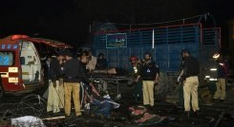 Pakistani policemen and volunteers move the bodies of victims at the site of a bomb explosion in Lahore on February 13, 2017