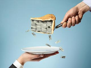 One businessman serving pie full of money to other holding plate, studio shot