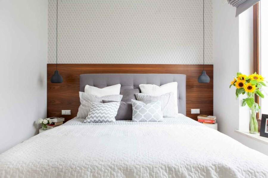 W sypialni, ścianę za tapicerowanym wezgłowiem łóżka zdobi tapeta w delikatny, geometryczny wzór oraz płyta fornirowana orzechem.