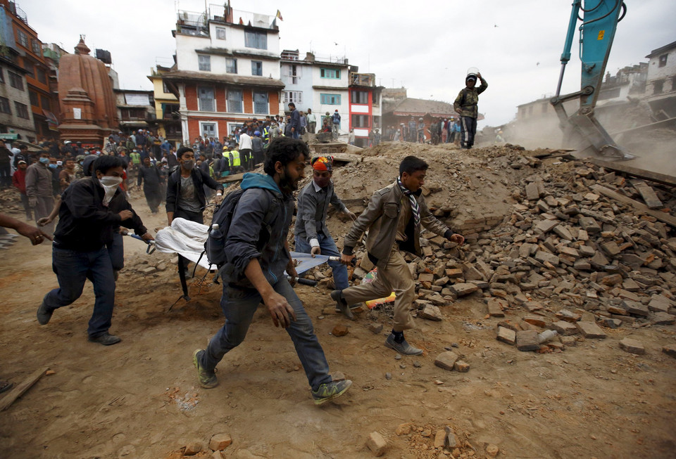 People carry the body of a victim on a stretcher, which was trapped in the debris after an earthquake hit, in Kathmandu, Nepal