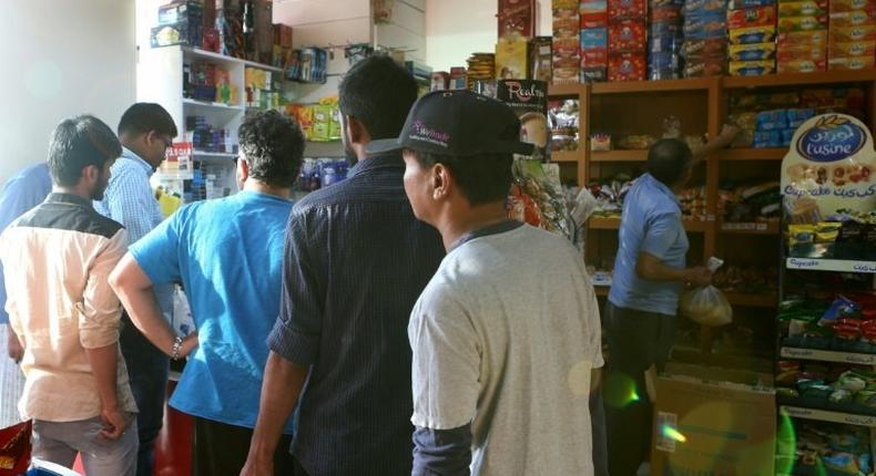 People buy snacks at a shop in Qatari capital Doha on June 5, 2017 as the gas-rich Gulf state grappled with a diplomatic crisis after its neighbours cut ties