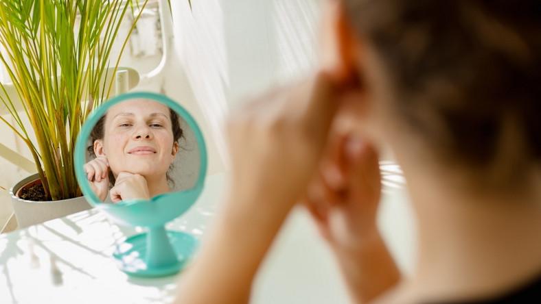 Kobieta przed lustrem. Trening twarzy
