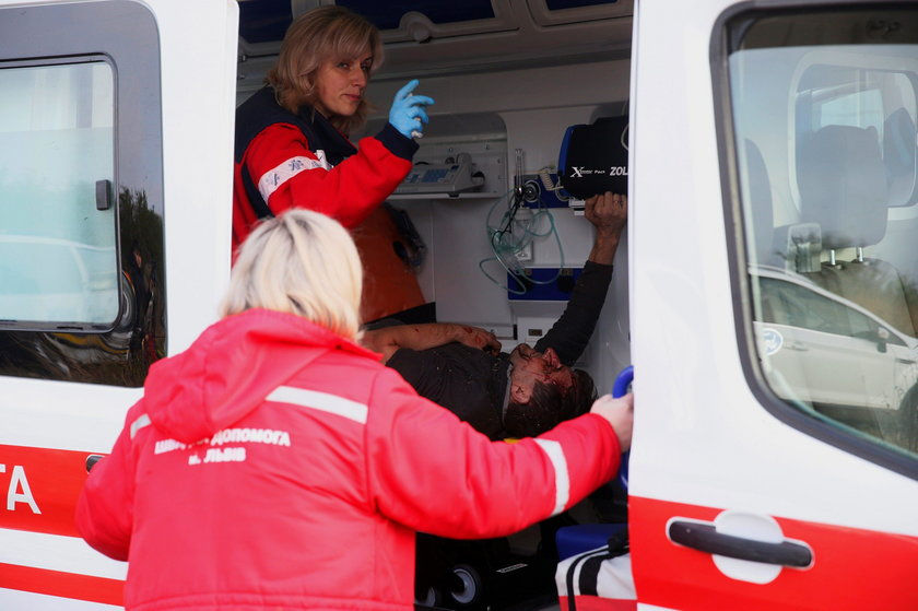 Medics assist a wounded person at the site of the Antonov-12 cargo airplane emergency landing in Lvi