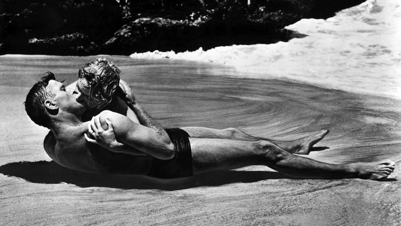 """Burt Lancaster namiętnie całuje wśród fal filigranową Deborah Kerr –to najsłynniejsza scena erotyczna Hollywood lat 50. Nie znajdziemy chyba ani jednego rankingu na najważniejsze pocałunki w dziejach kina, w których """"Stąd do wieczności"""" nie zajęłoby miejsca na podium. Na liście serwisu College Candy jest tym najwspanialszym w historii."""