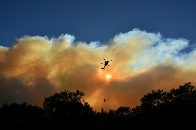 On November 11, 2018 a helicopter makes a water drop on the wildfires in the Feather River Canyon, east of Paradise, California