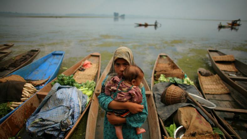 Indie. Dziewczynka trzyma na rękach siostrzyczkę na targu przypraw