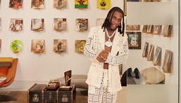 Burna Boy poses against the backdrop of old records for Architectural Digest