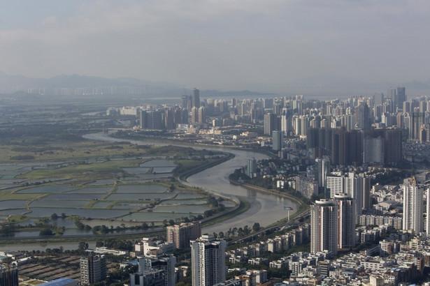 Gdy w 1977 roku Deng Xiaoping odwiedzał Shenzhen, była to tylko niewielka wioska rybacka, która funkcjonowała dzięki bliskości Hong Kongu, z którym graniczyła przez rzekę. Dostrzegając przepaść dzielącą warunki życiowe ówczesnej brytyjskiej kolonii i chińskiej osady, zdecydował o utworzeniu w Shenzhen specjalnej strefy ekonomicznej, która powstała w maju 1980 roku jako pierwszy tego typu obszar w Chińskiej Republice Ludowej. Po prawej stronie widzimy na zdjęciu budynki leżące w dzielnicy Luohu, sąsiadujące przez rzekę z obszarami uprawnymi należącymi do Hong Kongu.