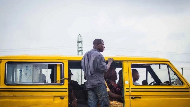 A Lagos 'Danfo' conveying people to their destination, 'Agbero' helps the driver.