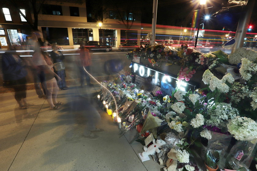 Fredericton residents pay their respects at a makeshift shrine in front of police headquarters