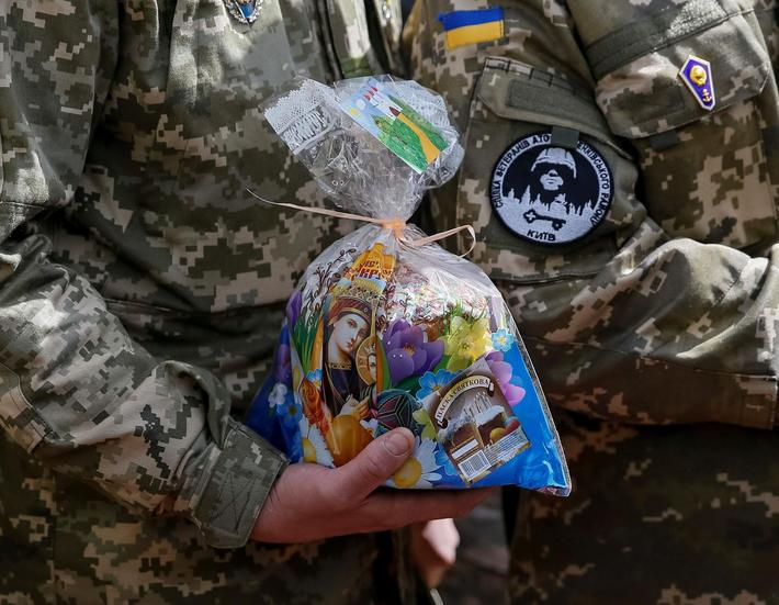 A Ukrainian serviceman holds an Easter cake during a ceremony to bless Easter cakes and eggs in cent