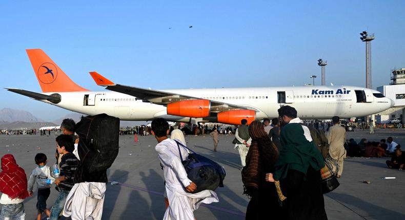 Afghan families walk by the aircrafts at the Kabul airport in Kabul on August 16, 2021, after a stunningly swift end to Afghanistan's 20-year war, as thousands of people mobbed the city's airport trying to flee the group's feared hardline brand of Islamist rule.