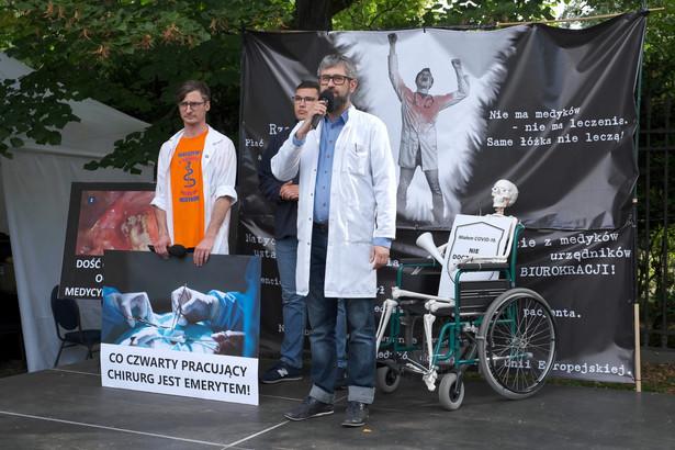 """Szef Porozumienia Rezydentów OZZL Krzysztof Hałabuz (C) podczas kolejnego dnia protestu pracowników ochrony zdrowia w tzw. """"białym miasteczku"""""""