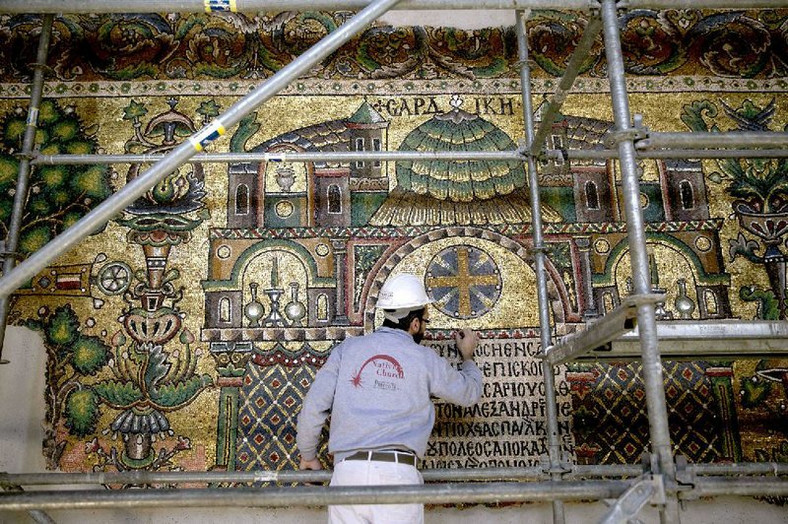 A restoration expert works on a mosaic inside the Church of the Nativity in Bethlehem. (The Arkansas Democrat-Gazette)
