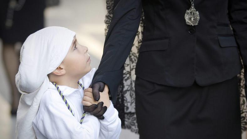 Chłopiec ubrany w strój członka bractwa religijnego idzie na procesję w Almerii