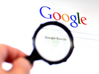 Hand holds Magnifying glass against Google homepage