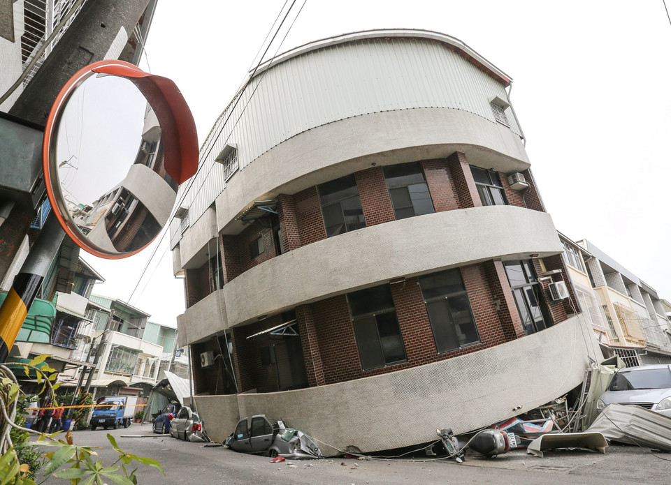 Crushed vehicles are seen under a building that was damaged after a powerful earthquake hit Tainan