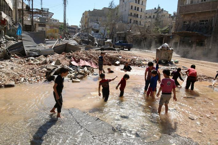 Children play with water from a burst water pipe at a site hit yesterday by an air strike in Aleppo