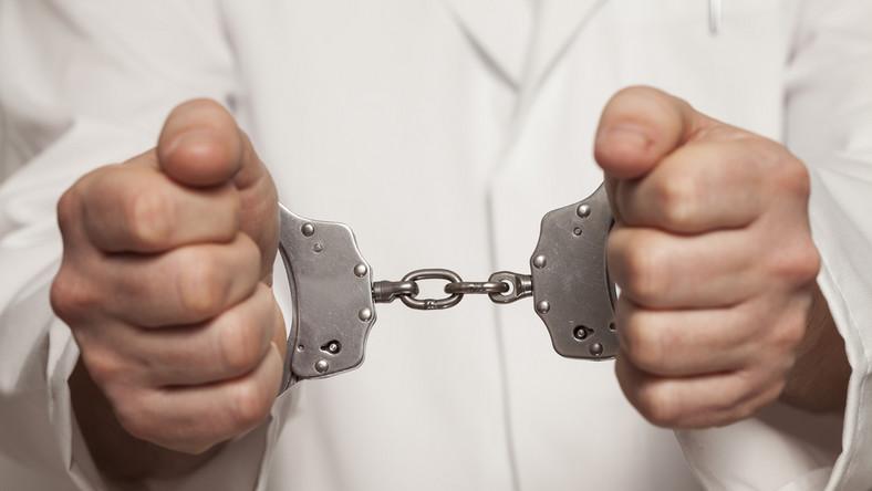 Lekarz zakuty w kajdanki  - zdjęcie ilustracyjne