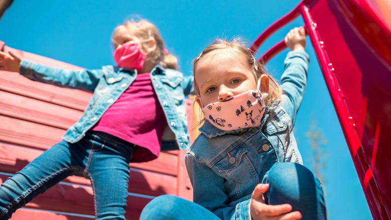 Dzieci w maseczkach bawią się na placu zabaw
