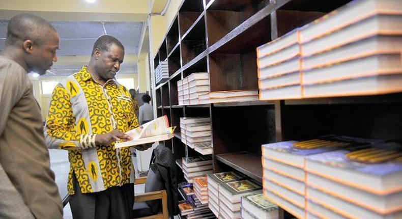 Dr Yaw Osei Adutwum, Deputy Minister in Charge of General Education glancing through a book at the Central Library in Accra with him is Mr Hayford Siaw,the Ag Chief Executive Officer of the GLA.
