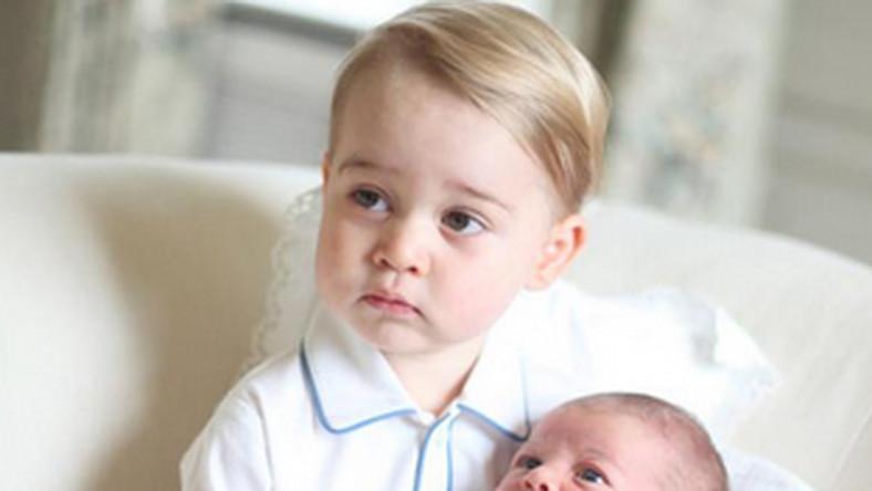 Jerzy, ubrany w biały komplet z niebieskimi elementami, siedzi na białej sofie, trzymając małą księżniczkę, ubraną w całości na biało. Na jednej z fotografii całuje ją w główkę. Zdjęcia wykonała osobiście ich mama- księżniczka Kate, jak informuje Pałac Kensington- w połowie maja w rodzinnej wiejskiej rezydencji Anmer Hall w hrabstwie Norfolk.