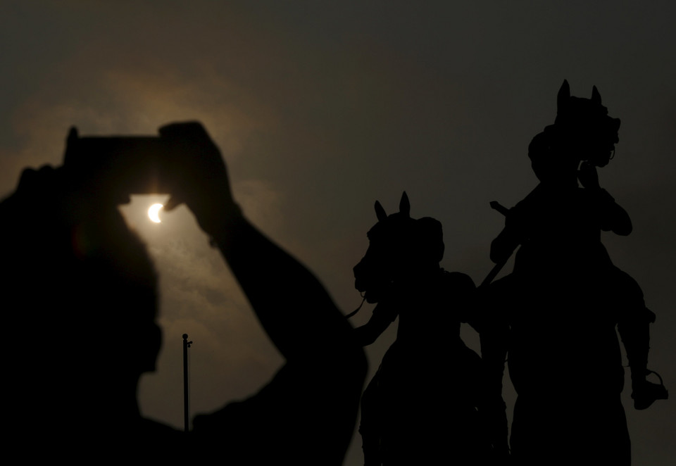 A man uses his smart phone to document a partial solar eclipse in Phnom Penh