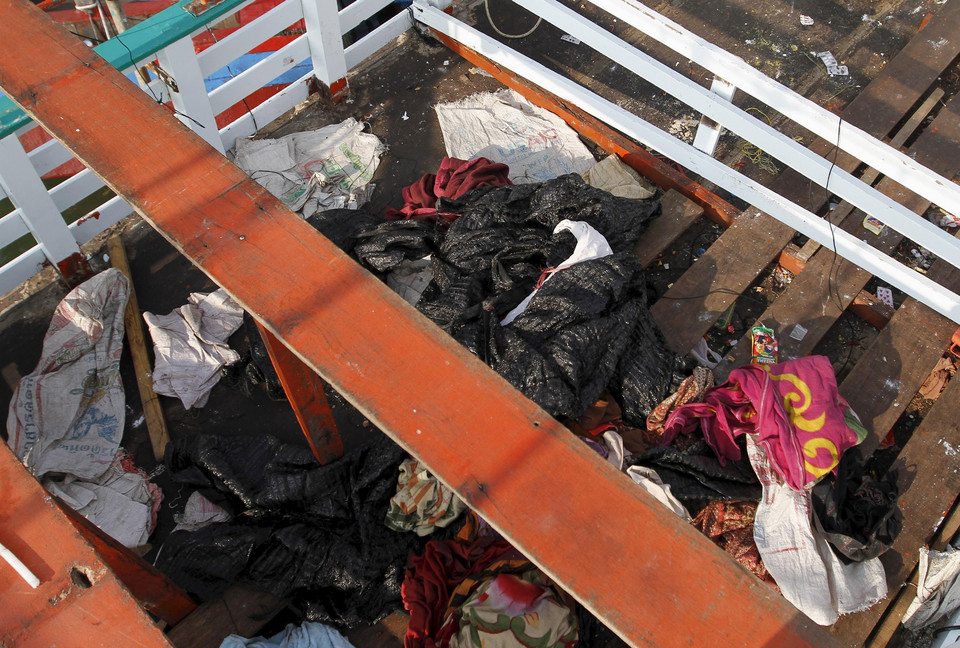 Discarded clothes and debris are seen on the deck of a fishing boat which carried Rohingya and Bangladeshi migrants to Indonesia, at a port in Lhokseumawe, Indonesia's Aceh Province