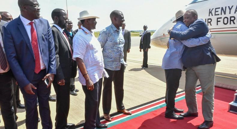 President Uhuru Kenyatta hugs ODM leader Raila Odinga