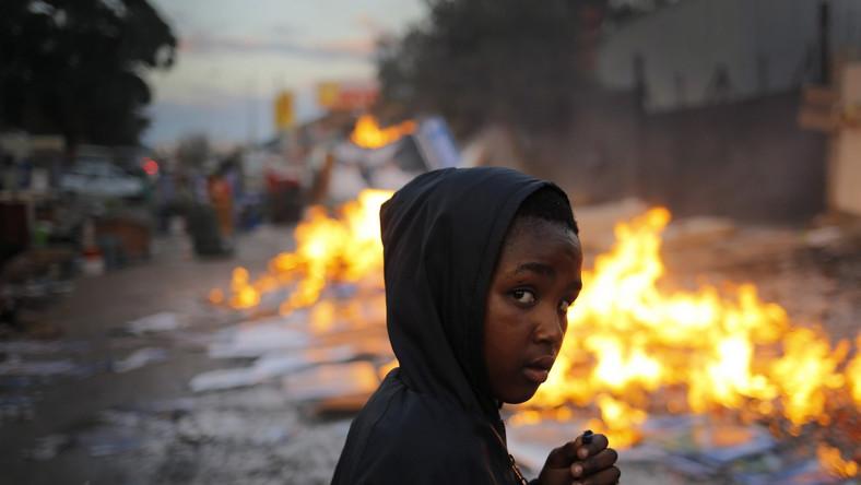 Mały mieszkaniec Johannesburga wśród ognisk, przy których ogrzewają się pozbawione schronienia rodziny; 5 czerwca 2014 roku...