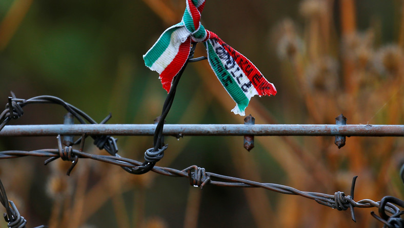 A small Hungarian flag adorns barbed wire at a memorial near the Andau bridge on the Hungarian-Austrian border