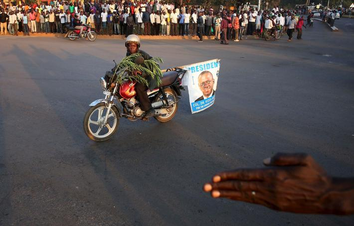 A supporter of opposition leader Kizza Besigye rides a motorbike in front of riot police in Kampala